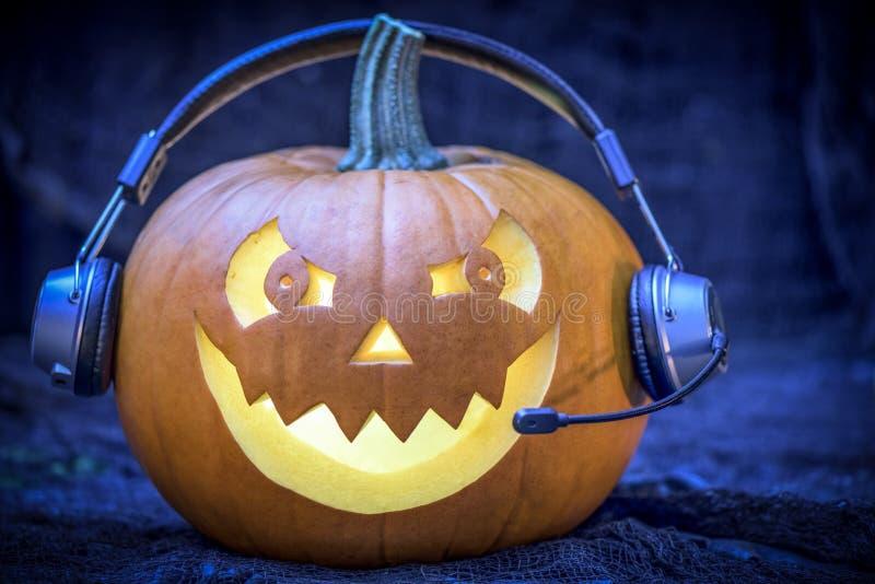 Calabaza en auriculares - postal de Halloween fotos de archivo