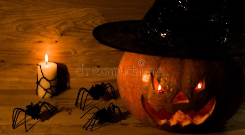 Calabaza espeluznante para Halloween en sombrero de la bruja en fondo de madera fotos de archivo libres de regalías