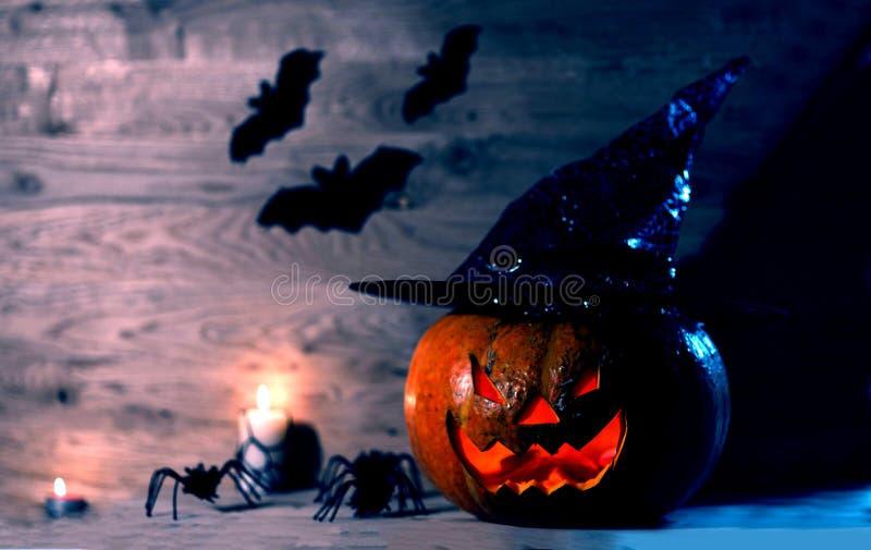 Calabaza espeluznante para Halloween en sombrero de la bruja en fondo de madera fotos de archivo