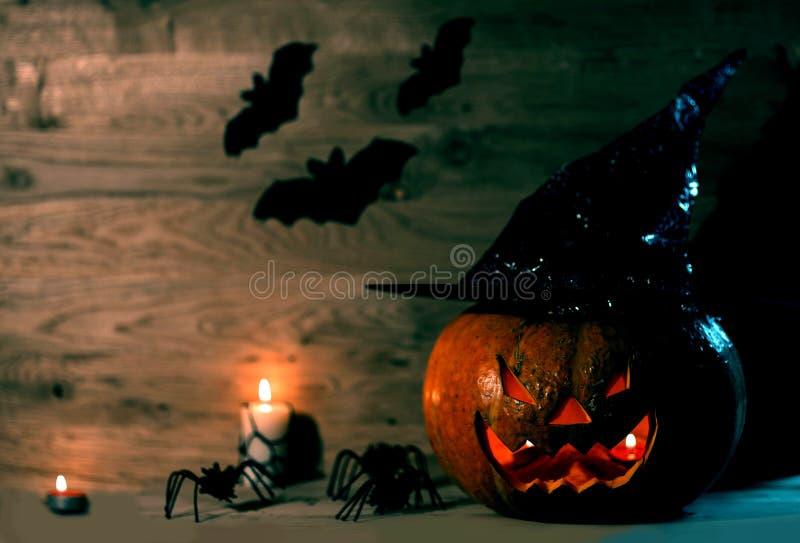 Calabaza espeluznante para Halloween en sombrero de la bruja en fondo de madera foto de archivo