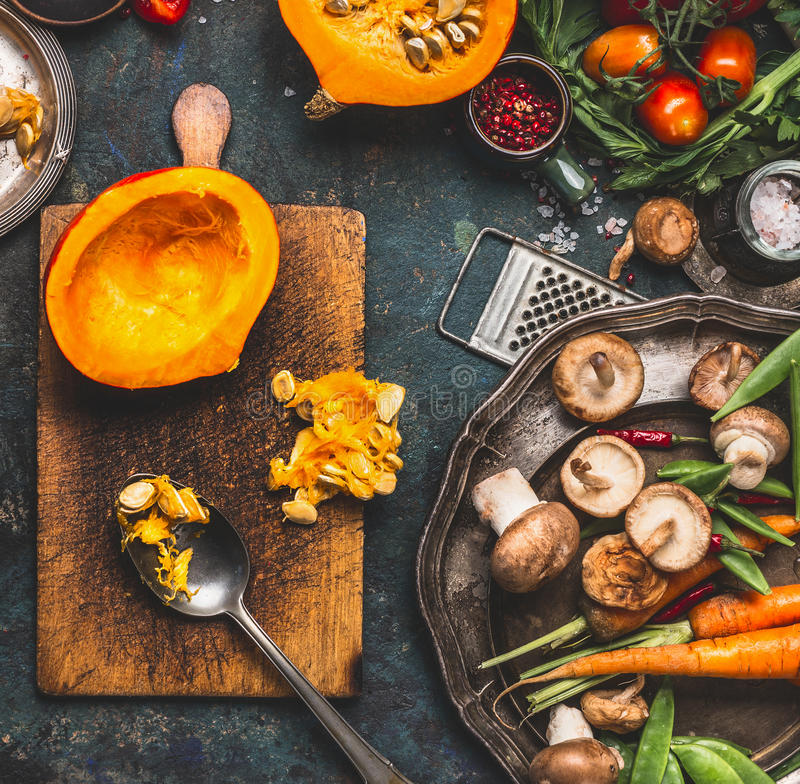 Calabaza media en tabla de cortar con la cuchara, las setas y los ingredientes de las verduras para cocinar vegetariano sabroso imagen de archivo