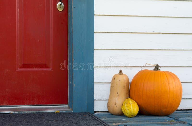 Calabaza y calabazas decorativas en el pórche de entrada de una casa fotografía de archivo