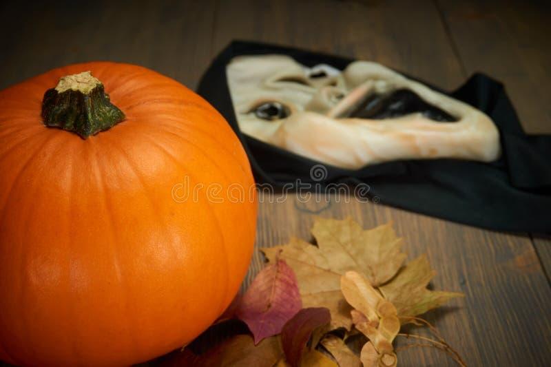 Calabaza y máscara de Halloween en la tabla de madera vieja fotografía de archivo