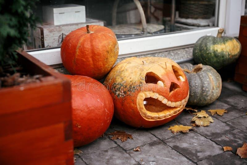 Calabazas con las caras asustadizas en calle de la ciudad, la decoración del día de fiesta de los frentes de la tienda y edificio imagenes de archivo