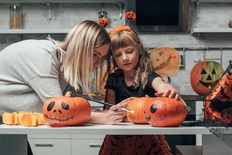 calabazas de pintura de la mujer joven y de la pequeña hermana para Halloween junto en cocina foto de archivo