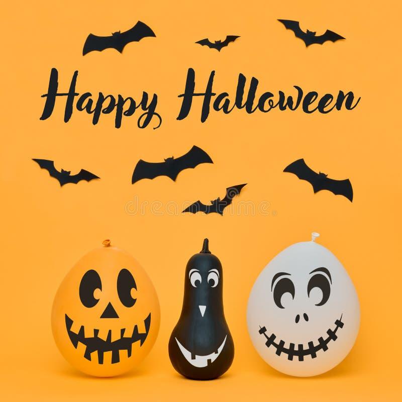 Calabazas lindas de Halloween con las caras divertidas y los palos sonrientes del papel que vuelan sobre fondo anaranjado Música  imagenes de archivo