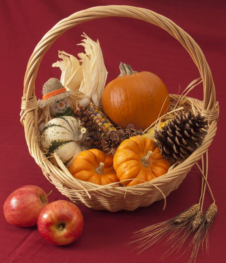 Calabazas, maíz, y muñeca del espantapájaros en cesta fotografía de archivo libre de regalías