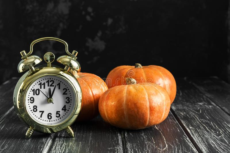 Calabazas y un despertador en una tabla negra rústica Tiempo de Halloween Foco selectivo fotografía de archivo