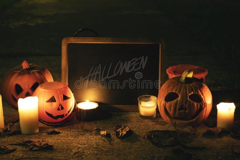 Calabazas y velas de Halloween con la pizarra fotografía de archivo