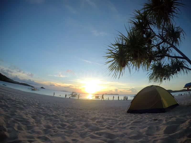 I watch the sunset alone. Calaguas, Camarines Sur. Daet and Paracale Towns. A safe haven. Fine Sand and clear waters. Sunset palm tress camping blue skies royalty free stock photos