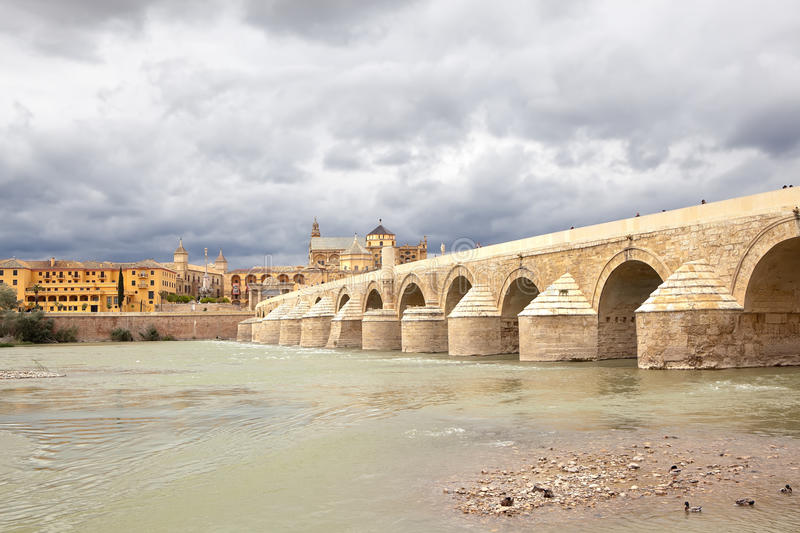 Calahorra Tower and the Roman bridge. Cordova. Spain. Cordova, Spain - May 29, 2013: a stone arch bridge across the river on which people walk. On the opposite stock images