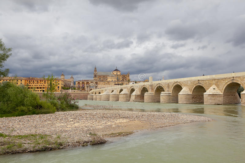 Calahorra Tower and the Roman bridge. Cordova. Spain. Cordova, Spain - May 29, 2013: a stone arch bridge across the river on which people walk. On the opposite royalty free stock photos