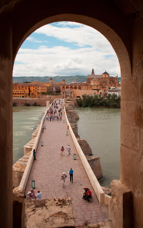 Calahorra Tower and the Roman bridge. Cordova. Spain. Cordova, Spain - May 29, 2013: a stone arch bridge across the river on which people walk. On the opposite stock image