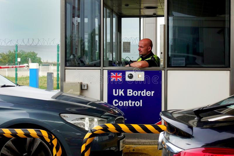 Calais, França - 12 de agosto de 2018: Membro da polícia BRITÂNICA da força da beira que verifica carros como aproximam o termina imagens de stock