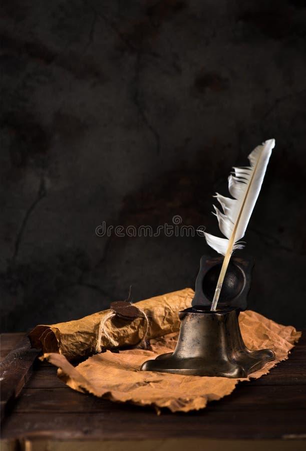 Calamaio antico con la penna della piuma e la vecchia carta da lettere immagine stock