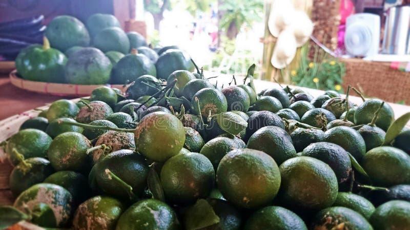 Calamansi (kalamansi) små citrusfrukter med guavabakgrund royaltyfria foton
