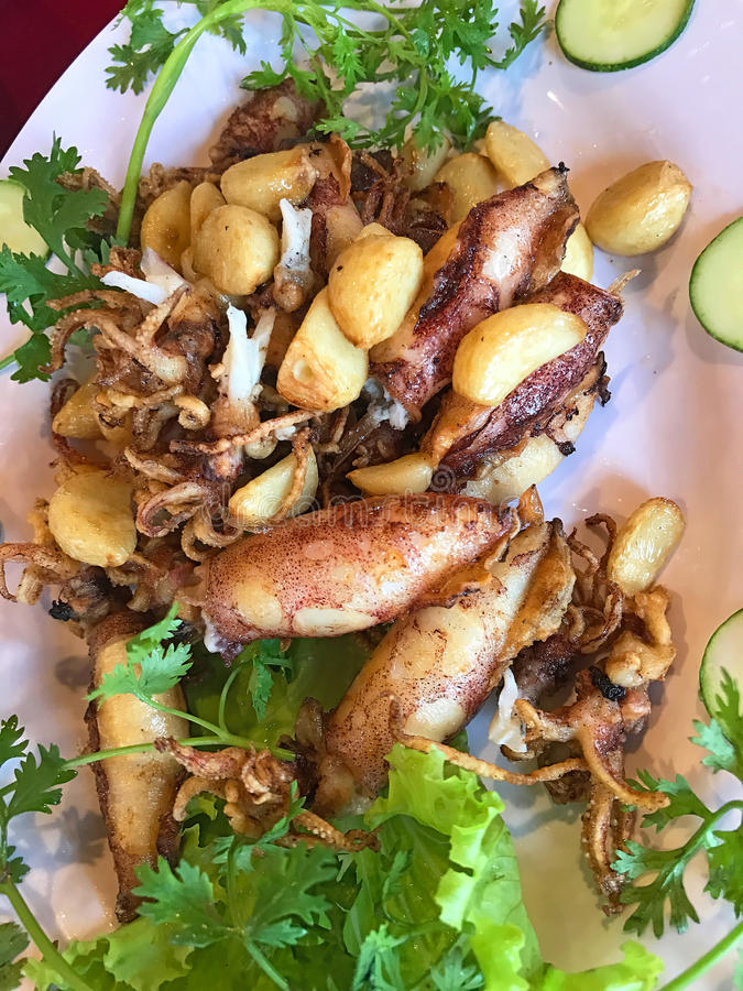 Calamar frito con la pimienta del ajo, rematada con el pepino y el coriandro fotografía de archivo libre de regalías