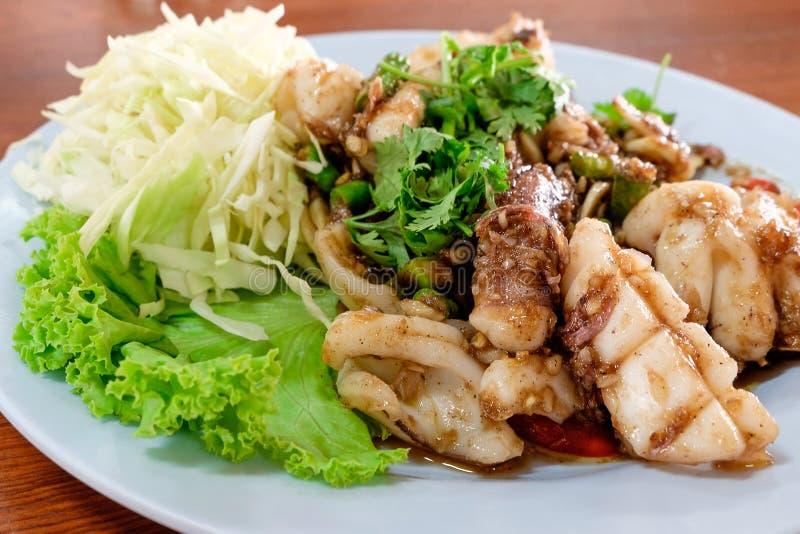 Calamar frito con pimienta negra y ajo en el plato blanco fotos de archivo