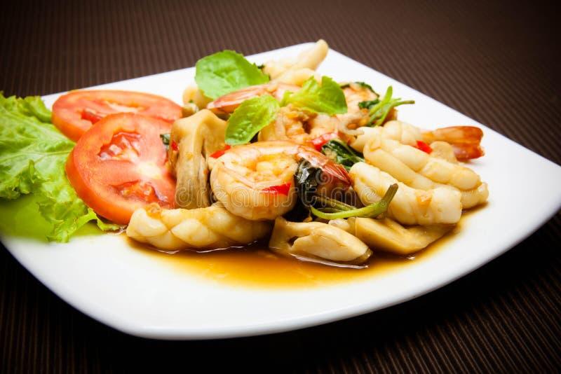 Calamar y camarón fritos picantes con las hojas de la albahaca imágenes de archivo libres de regalías