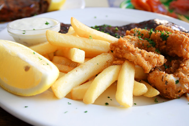 Calamari and chips. Deep fried calamari and chips together with juicy pork ribs on a plate royalty free stock photos