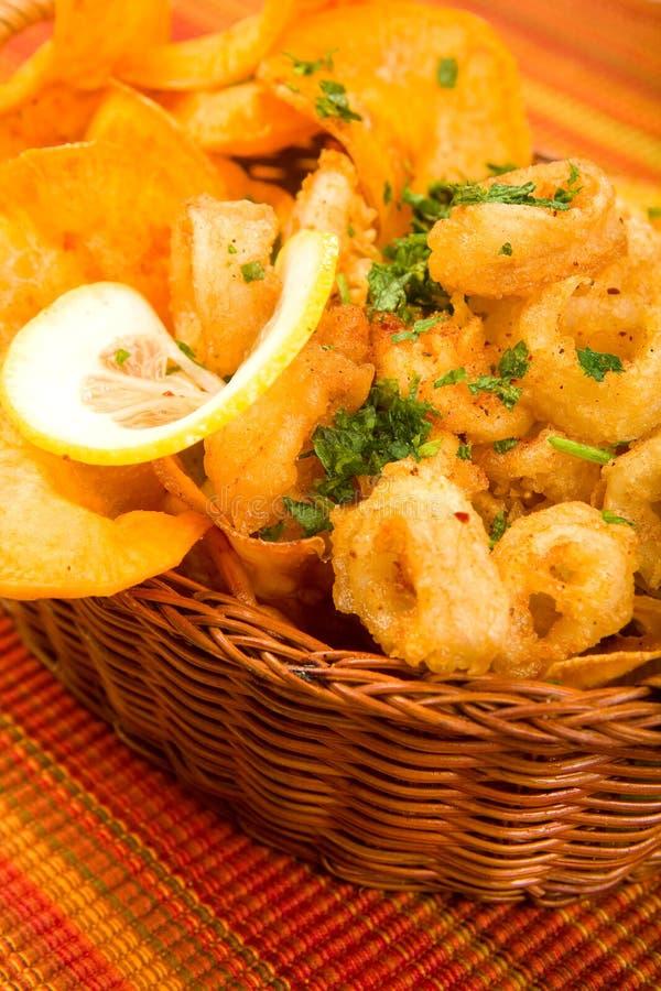 Calamari fritado com as microplaquetas de batata doce fotos de stock royalty free