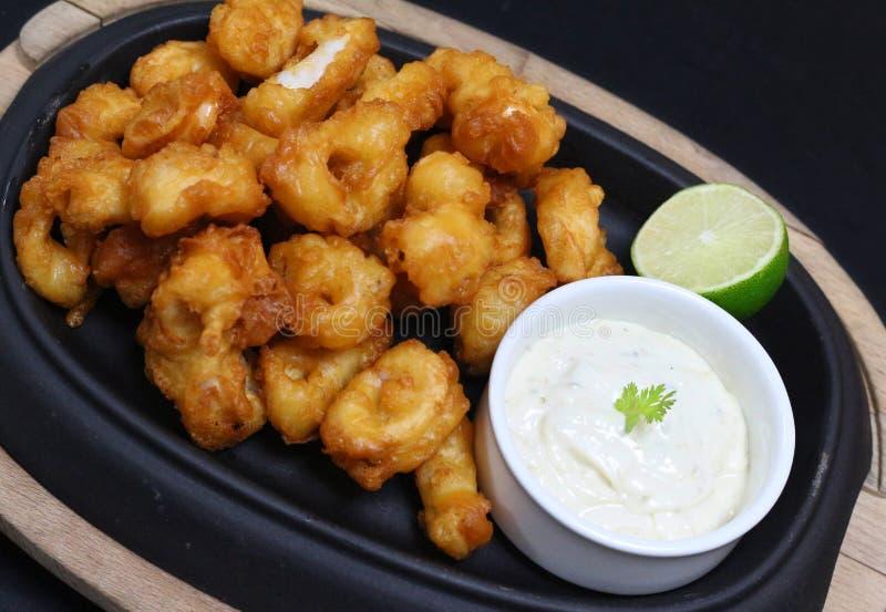 Calamari fritti nel grasso bollente della tempura con la salsa e la calce di tartaro immagine stock