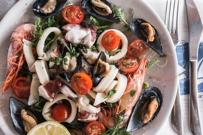 Calamari, octopus, mussels and shrimps with tomatoes and lemon. Delicious seafood salad with fork and knife top view. stock photo