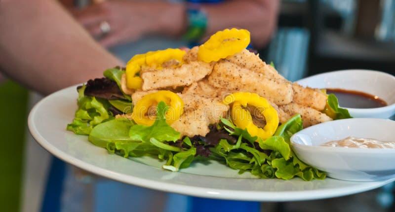 Calamari recién preparado y pimientas cortadas con verdes de la ensalada imagen de archivo