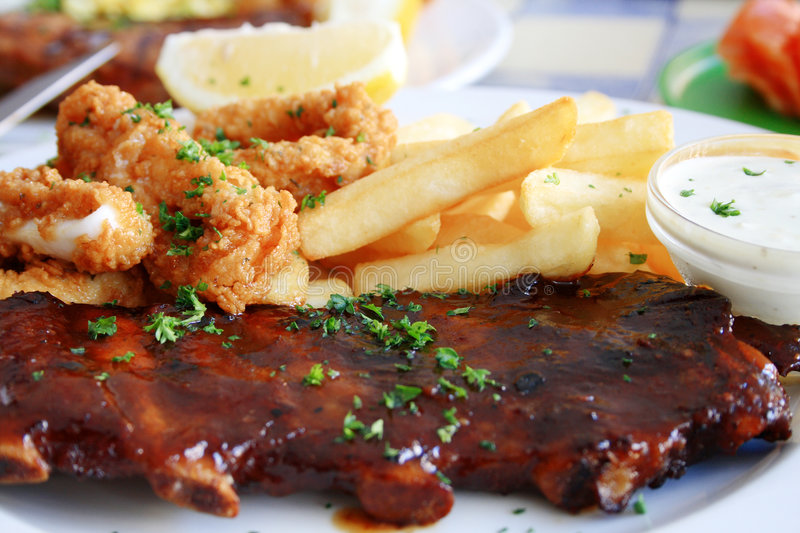 Calamari, ribs and chips. Deep fried calamari and chips together with juicy pork ribs on a plate stock photo