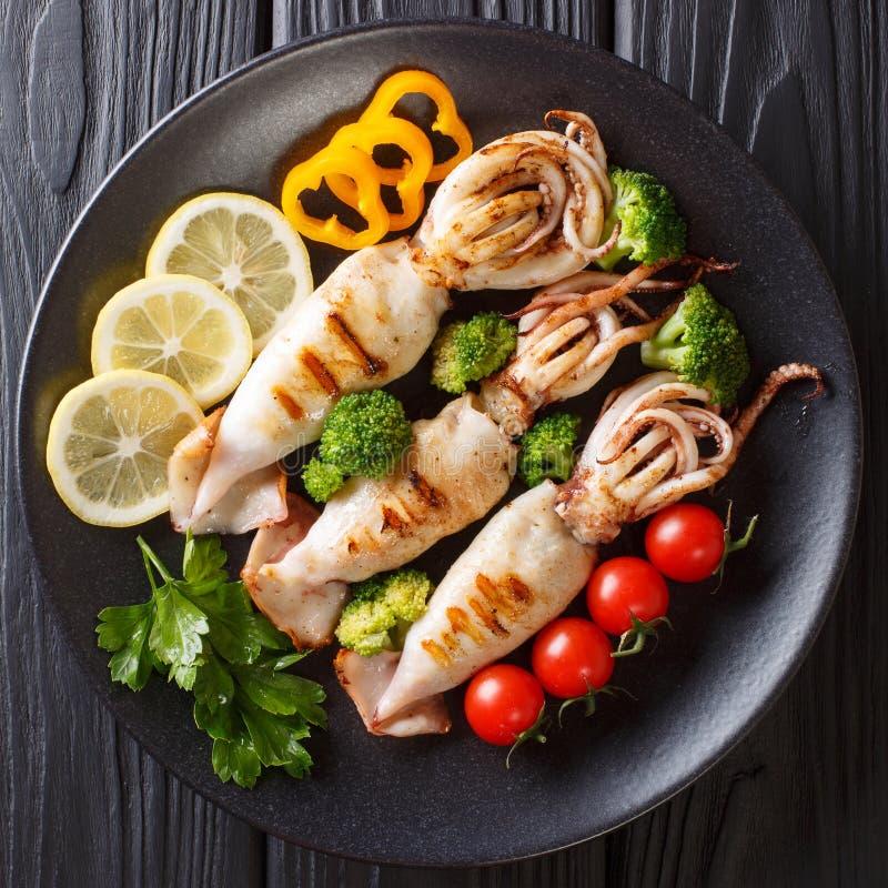 Calamaro arrostito con il primo piano degli ortaggi freschi su un piatto la cima rivaleggia fotografie stock libere da diritti