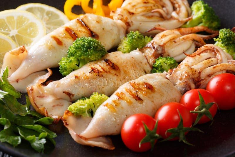 Calamaro arrostito con il primo piano degli ortaggi freschi su un piatto orizzonte fotografia stock