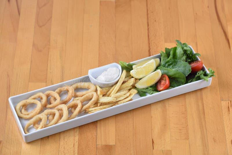 Calamary Fish. Served with potato, lemon and salad stock photography