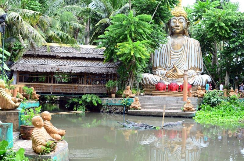 Stone Buddha decorates an Asian aquatic jungle theme park royalty free stock photo