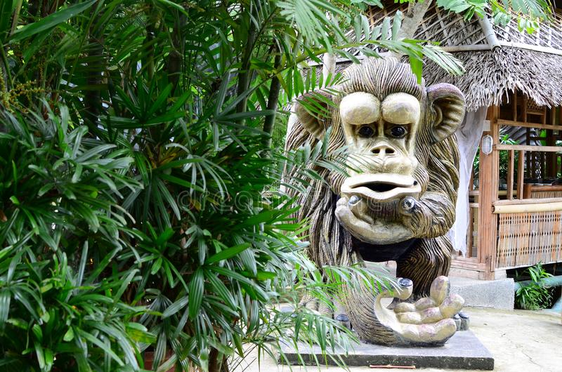 Huge concrete carved monkey statue in an Asian aquatic jungle theme park royalty free stock photography