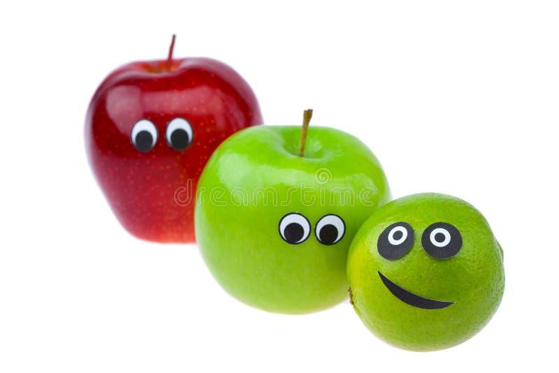 Calce e mela con gli occhi ed i fronti immagine stock