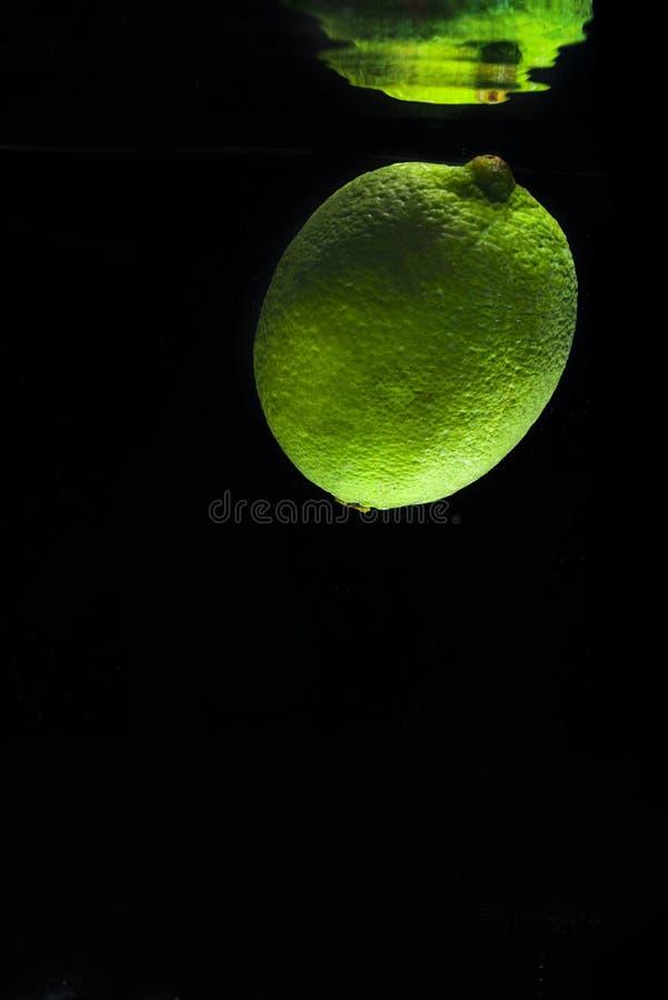 Calce verde fresca in acqua con la riflessione di specchio fotografia stock