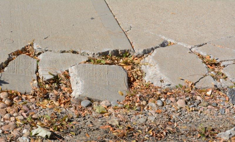 Calcestruzzo rotto del marciapiede in autunno fotografia stock