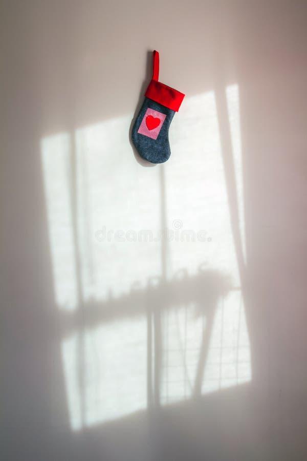 Calcetín rojo de la Navidad con una ejecución del corazón en la pared blanca con shado imagen de archivo libre de regalías
