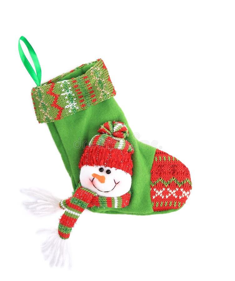 Calcetín verde de la Navidad con el muñeco de nieve. imagen de archivo