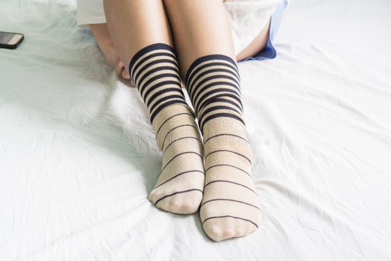 Calcetines del desgaste de la mano de la mujer en cama fotos de archivo