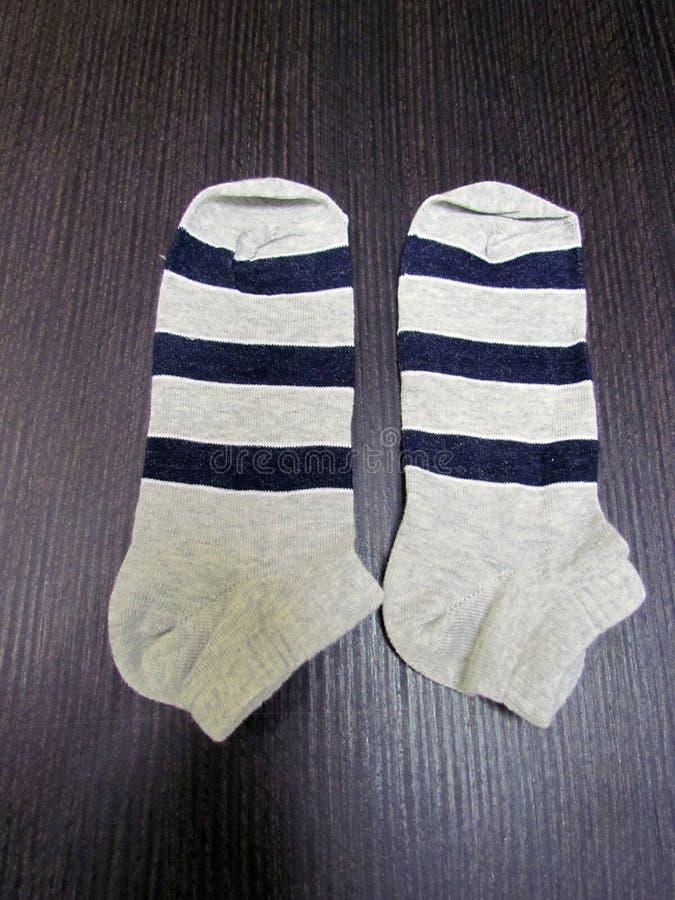 Calcetines grises del bebé con las rayas azules fotografía de archivo libre de regalías