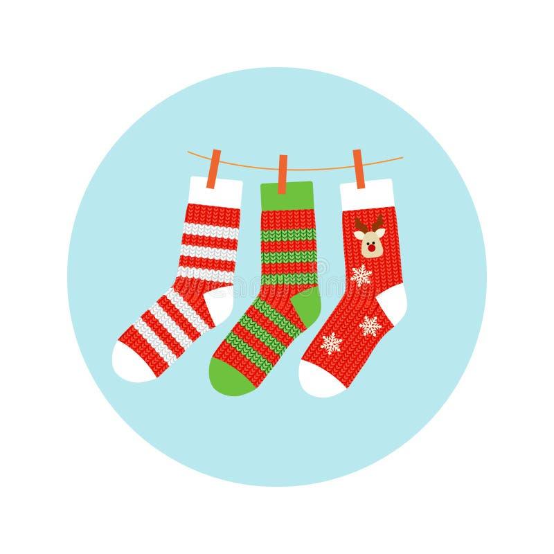Calcetines hechos punto con un ciervo y una tira, rojos con el verde, colgando en una cuerda La Navidad pega el fondo del vector  ilustración del vector
