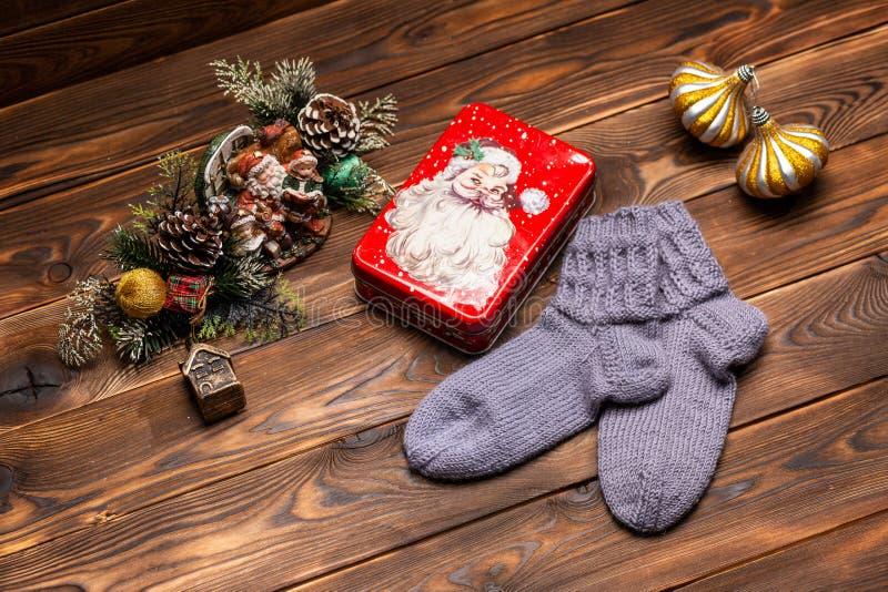 Calcetines hechos punto de lana grises, decoraciones de la Navidad y una caja del metal con la imagen de Santa Claus en un fondo  fotografía de archivo