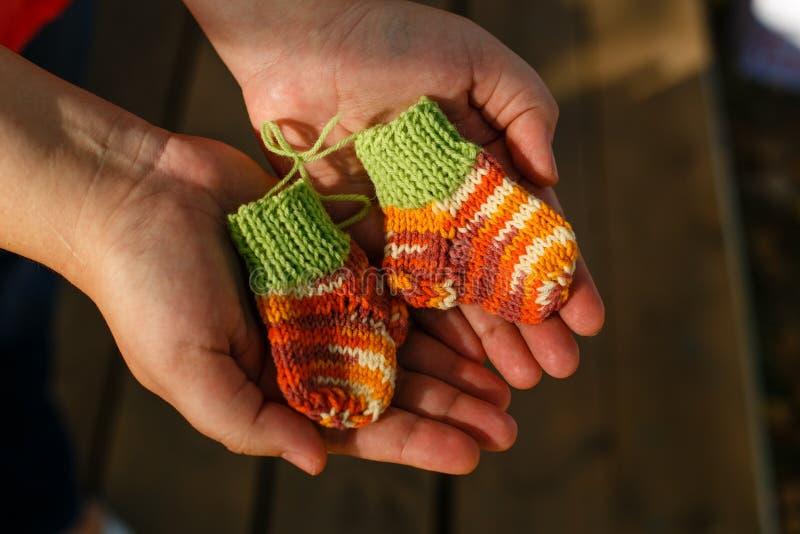 Calcetines hechos punto para los bebés prematuros en las manos fotos de archivo libres de regalías