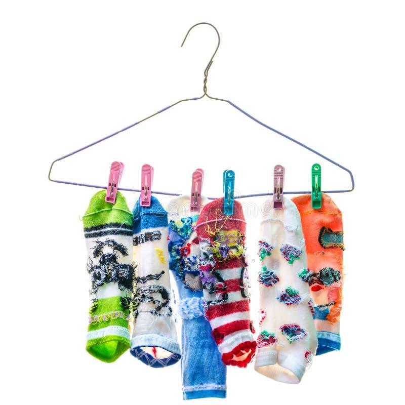 Calcetines que cuelgan en una cuerda para tender la ropa en el fondo blanco imagen de archivo