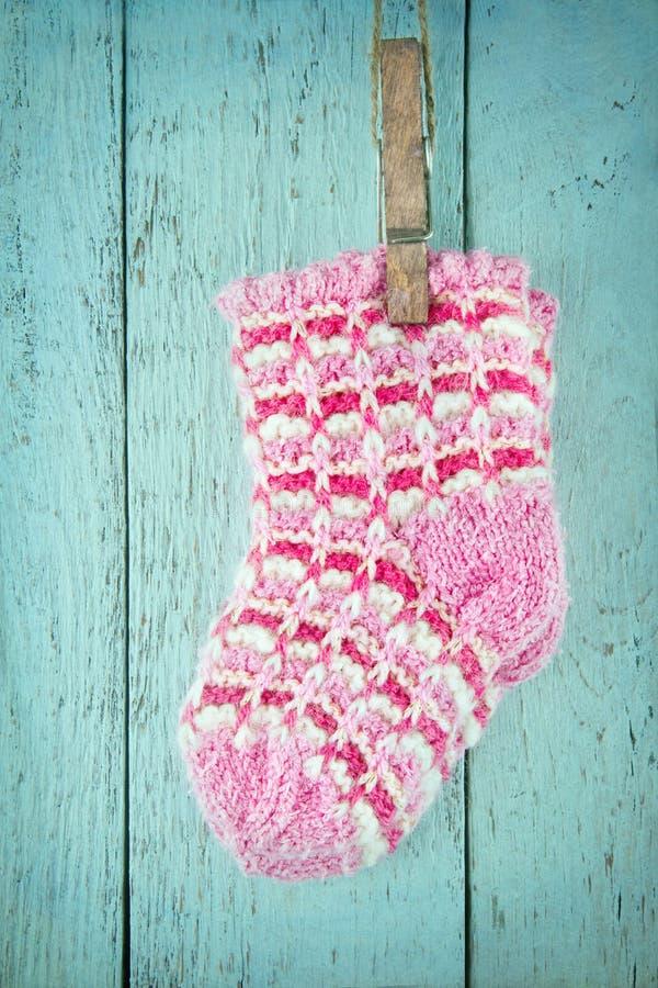 Calcetines rosados del bebé en un fondo azul foto de archivo