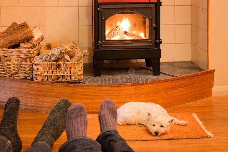 Calcetines y pies de un par que se relaja por el fuego con la montaña del oeste t foto de archivo