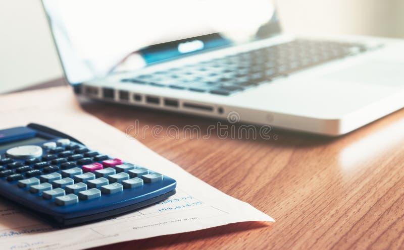 Calciador y ordenador portátil en el escritorio foto de archivo