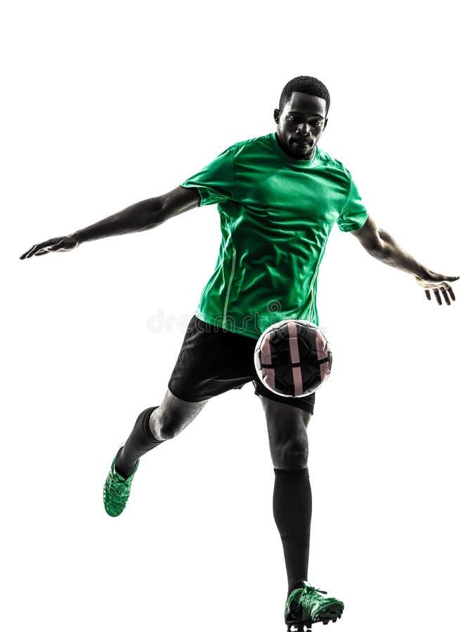 Calciatore africano dell'uomo che dà dei calci alla siluetta fotografia stock libera da diritti