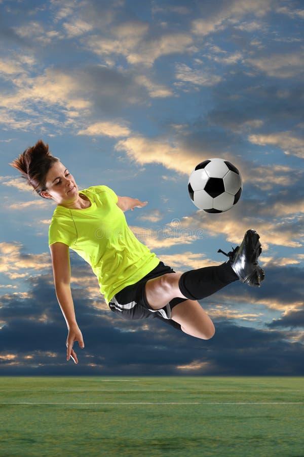 Calciatore femminile che dà dei calci alla palla fotografia stock